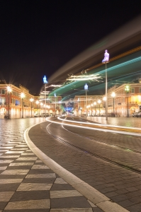 Place Masséna showing art installation of giant glowing buddhas on plinths by Jaume Plensa and long exposure of tram lights