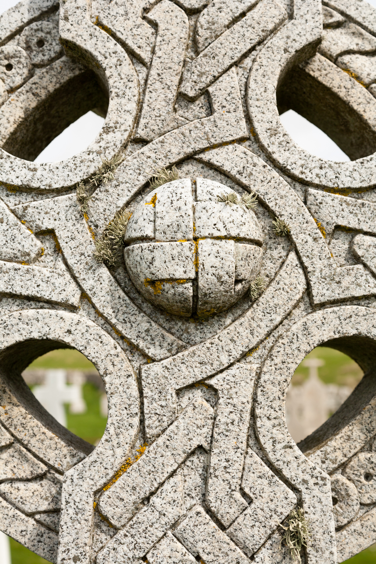 Close up showing the detail of Celtic cross grave in Barra cemetary. Moss and weathered rock visible.