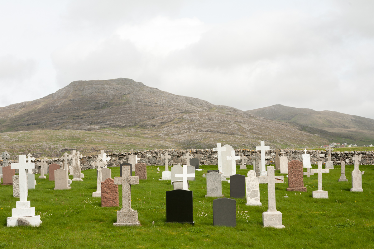 Barra cemetery showing the graves facing the land, the drystone wall and the background hills