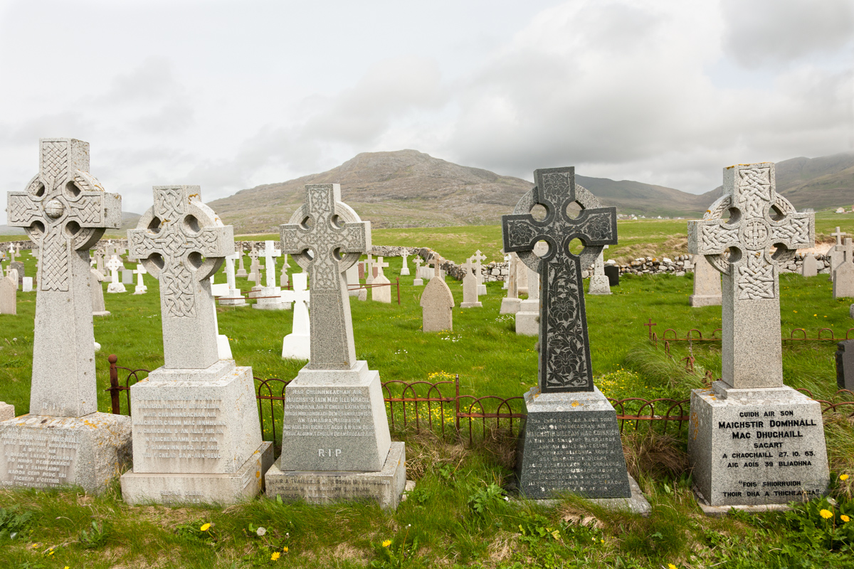 Barra cemetery with a close view of 5 prominent celtic cross engraved graves facing the sea. All the other graves face the land.