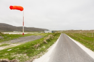 The Barra airport windsock in strong winds and the road leading up to the airport. The landing strip on the beach is just visible on the left.