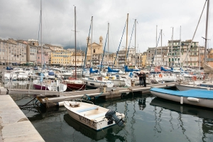 Photo taken in Bastia Corsica down by the harbour showing a profusion of boats and with many buildings in the backdrop.