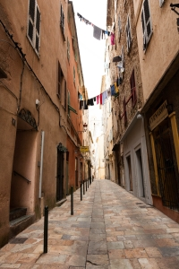 View up a street in Bonifacio Corsica with washing strung up between the houses.
