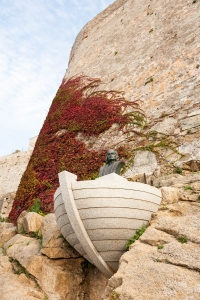 Sculpture of Christopher Columbus, in boat, protuding from wall with red ivy climbing behind.