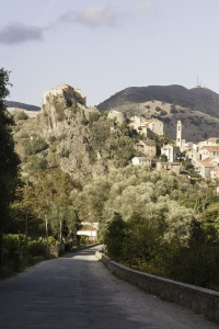 View from the Gorges de la Restonica showing the castle of Corte perched on a rocky cliff surrounded by the town below.