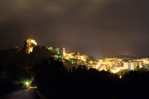 Photo of Corte castle taken at night showing the village and castle illuminated.