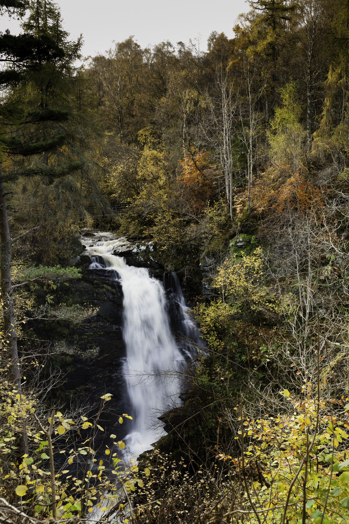 Large waterfall cascading seen across the valley from the path at Birks of Aberfeldy.